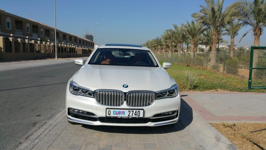 BMW 740 LI white in dubai beside trees